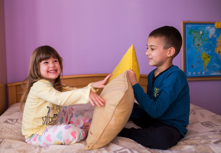 brother sister fight: Brother and sister having fun in a pillow fight. Little boy is holding a pillow, while the girl  hits him with her pillow. Both are wearing their pajamas  Happy children in a pillow fight Stock Photo