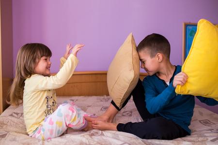 peleando: Hermano y hermana que se divierten en una pelea de almohadas. El niño pequeño está sosteniendo una almohada, mientras que la niña le golpea con su almohada. Ambos están usando sus pijamas Niños felices en una pelea de almohadas