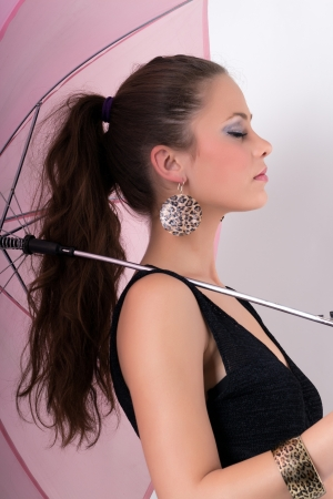 Beautiful young girl with umbrella posing in studio photo