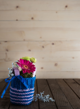 countrified: Small bouquet with gerbera and chrysanthemum in blue knitted vase on countrified wooden table Stock Photo
