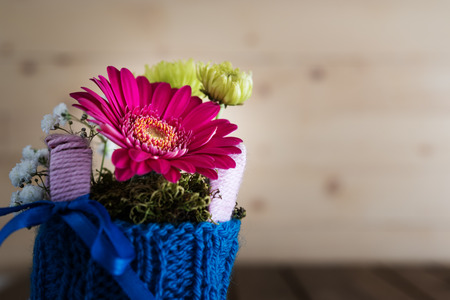 countrified: Closeup on small bouquet with gerbera and chrysanthemum in blue knitted vase on countrified wooden table Stock Photo