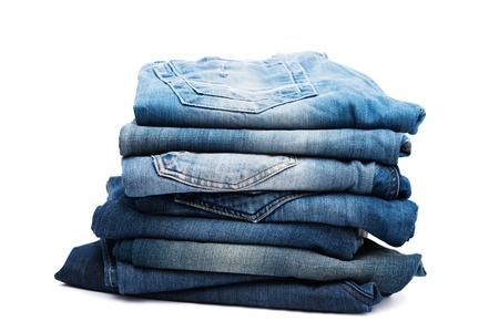 worn jeans: Stack of jeans isolated on white with shadow
