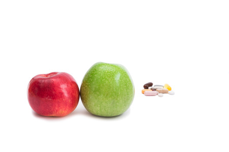 Green and red apples on foreground and group of pills on background, focus on apples photo