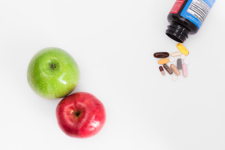 Green and red apples from one side and bottle with pills on other side, top view photo
