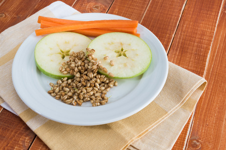 plato de comida: Apple, zanahoria y brotes de trigo en un plato blanco, mesa de madera