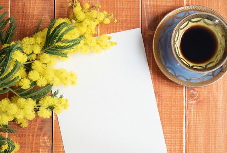 color wall: Empty card with mimosa and coffee on wooden background