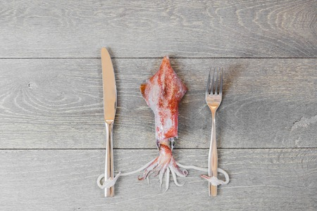 Fresh squid on wooden table holding fork and knife
