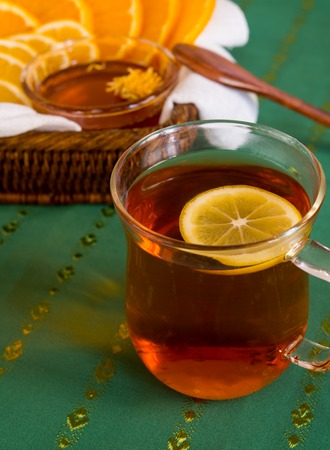 Cup of tea and citruses with honey on green tablewear photo