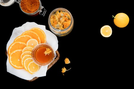 Basket with honey, sliced lemon and orange, jar with dry flowers of calendula, whole lemon and jar with powdered spices photo
