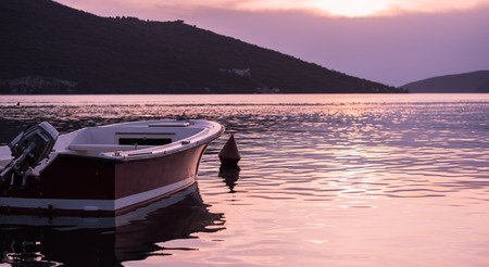 motor boat: Lonely motor boat on calm sea, pink sunset