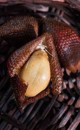 salak: Half-opened salak and two behind on wicker background Stock Photo