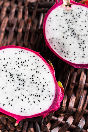 pitahaya: Two slices of ripe pitahaya on wicker background Stock Photo