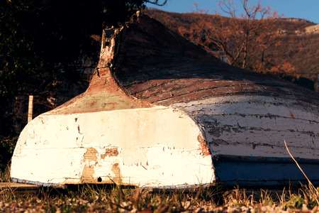 upturned: Old boat with cracked paint upturned on grass, sunset