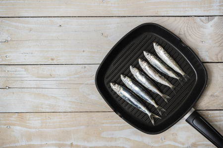 sardinas: Sartén con sardinas en fondo de madera Foto de archivo