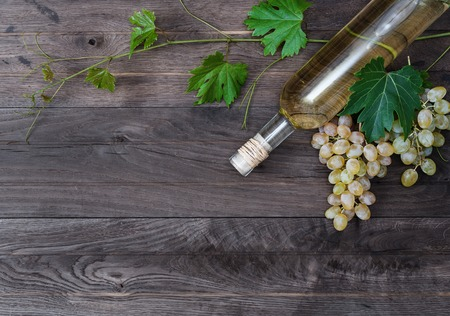 Bottle of white wine, grapevine and fresh grape on wooden background