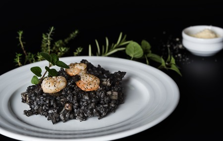 Plate with black risotto on black background with dramatic side light, aroma herbs and grated parmesan around plate