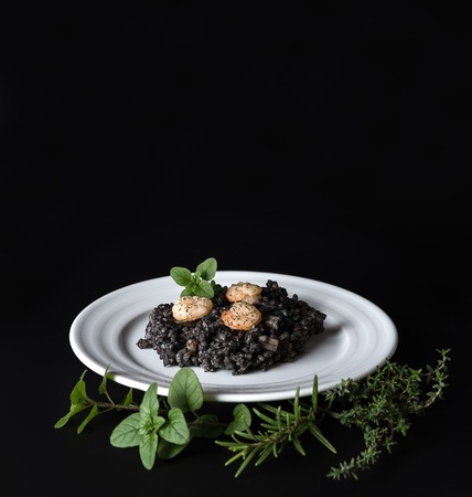 Plate with black risotto on black background with dramatic side light, aroma herbs around plate