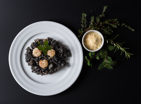 side plate: Plate with black risotto on black background with dramatic side light, aroma herbs and grated parmesan around plate