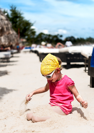 bandana girl: Four years old girl in t-shirt and bandana playing with sand on the beach Stock Photo