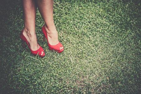 pies sexis: Las piernas de la mujer en zapatos rojos brillantes con tacones altos cruzadas sobre la hierba, tonos, vi�etas Foto de archivo