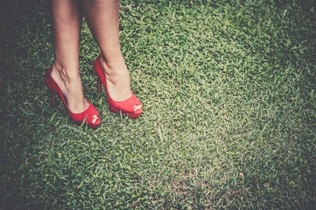 pies sexis: Womans legs in bright red shoes with high heels crossed on grass, toned, vignetting Foto de archivo
