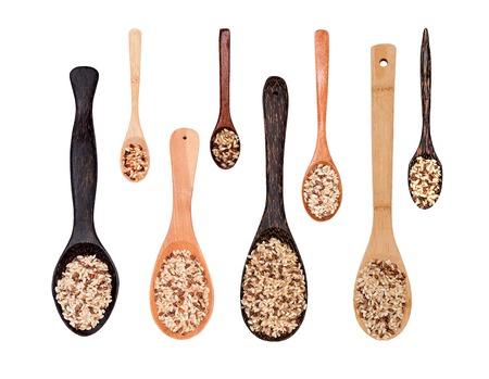 trompo de madera: Conjunto de arroz integral crudo aislado en diferentes cucharas de madera, vista desde arriba Foto de archivo