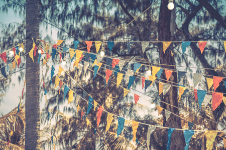 Decorative triangular flags and lamps on trees, toned