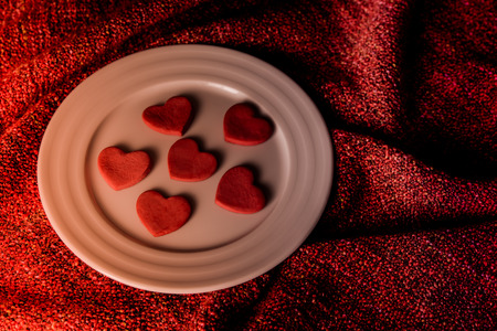 under heart: Cookies in shape of heart on white plate and red blanket under, light from fireplace Stock Photo