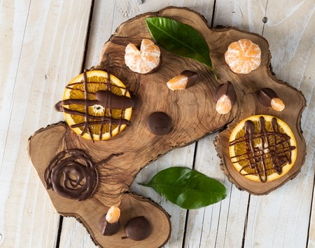 orange peel clove: Top view on citruses with chocolate on wooden board Stock Photo