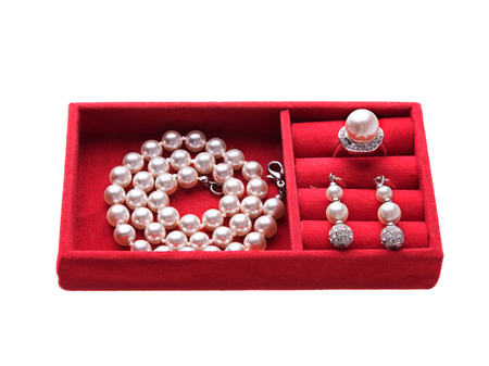 donna ricca: Jewelry box with pearl necklace, ring and ear-rings, white background