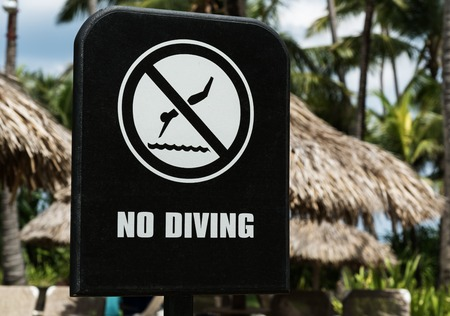 no diving sign: Warning sign NO DIVING with palms behind Stock Photo