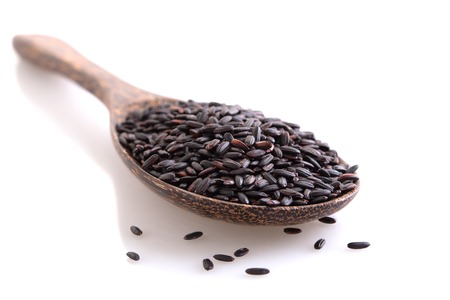 Black rice on wooden spoon, closeup, shallow DOF