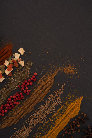 Mix of spices in a rows on black board