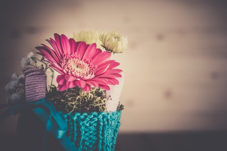 countrified: Small bouquet with gerbera and chrysanthemum in blue knitted vase on countrified wooden table, vintage toning