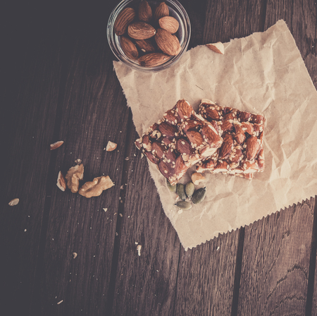 countrified: Nut bar with nuts on wooden table, vintage toning
