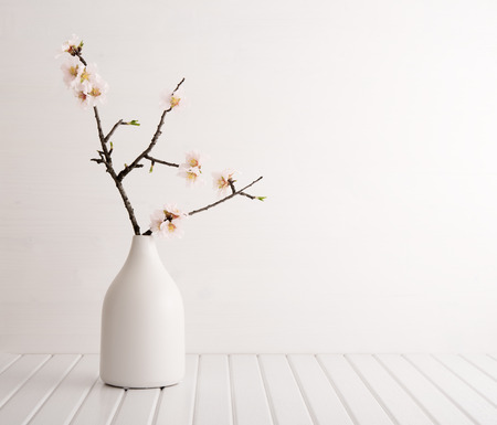 Vase with cherry blossom on wooden background Stock Photo