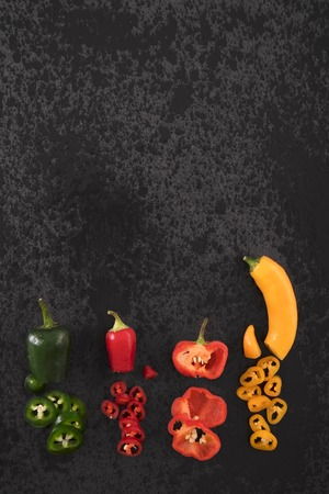 hottest: Different chili peppers on black stone background