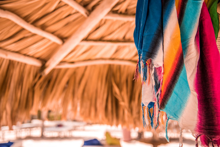 pareo: Bright multicolored pareo under sunshade from palm leaves, toned