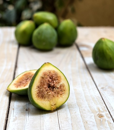 cutted: Cutted ripe green figs on rustic wooden table