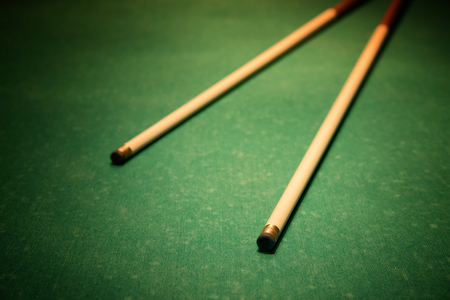 billiards cues: Cues for billiards on green table, vignette