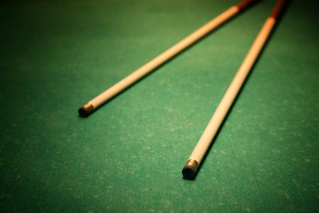 vignette: Cues for billiards on green table, vignette