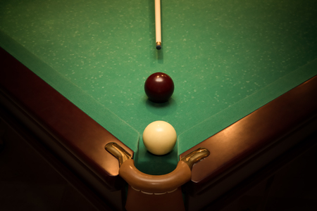 billiards cue: Balls and cue for russian billiards on green table near with hole, vignette