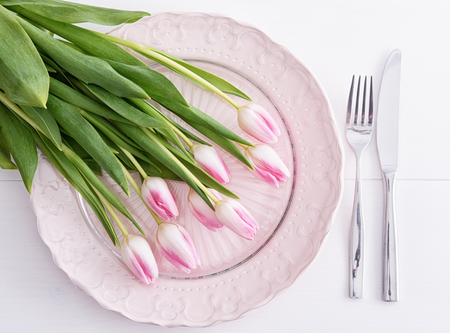 Top view on pink tulips on pink plate