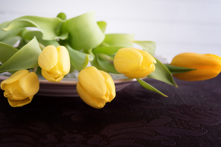 Fresh yellow tulips on plate, violet table-cloth Stock Photo