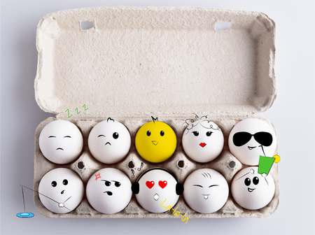 Box of white eggs with hand drawned faces on them