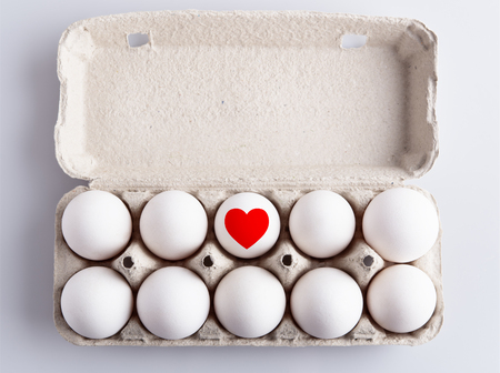 Box with white eggs and drawing of heart on white background Imagens