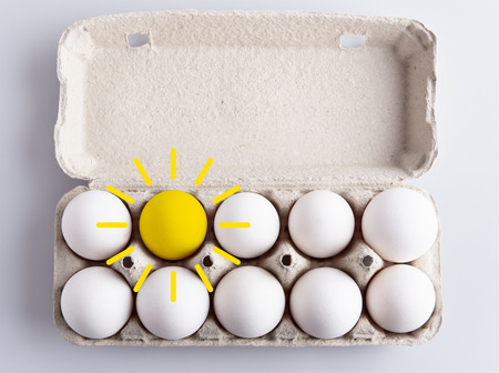 Box with white eggs and drawing of sun on white background