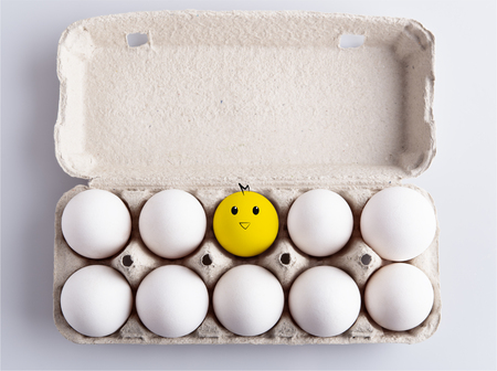 Box with white eggs and drawing of chicken on white background