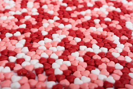 Background from red, white and pink bonbons in shape of heart