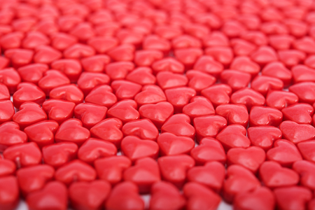 Background from red bonbons in shape of heart
